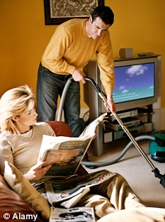 Bad woman sits reading newspaper while her poor, poor male partner does the vaccuuming around her. Abuser!