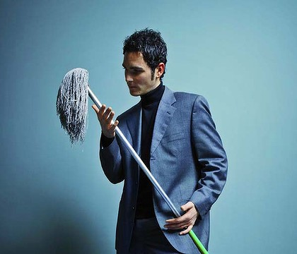 bizarre image of a very dapper young man in beautiful suit holding a mop and looking poetically sad, oh how low he has sunk