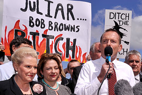 "Aust Opposition leader Tony Abbott standing with Lib MPs Bronwyn Bishop and Sophie Mirabella in front of a placard painted with flames and ""JuLIAR Bob Browns BITCH"""