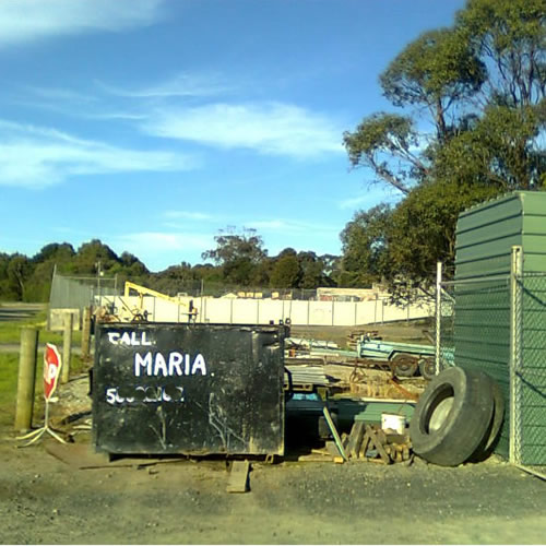 "Industrial bin in a rural setting with ""Call Maria"" and a phone number on it."