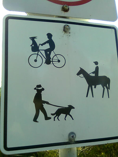 Sign on the Great Southern Rail Trail at Meeniyan showing a silouhette image of a person on a bike with a dog in the baskegt.