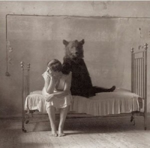 A woman sitting on a bed with a bear behind her