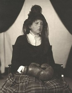 Woman sitting in a parlour or sitting room, wearing nineteenth century clothes, black veil and boxing gloves