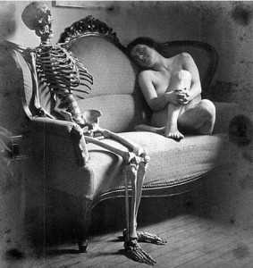 Naked woman on couch gazing at a seated skeleton
