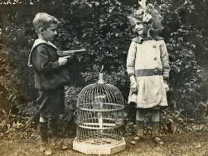 Little boy aiming a large toy (we hope) gun at a little girl, who is smiling happily. There is a bird cage on the ground between them.