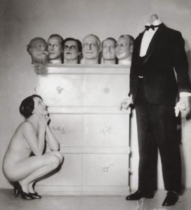 Woman with a headless male body and several heads arranged on a shelf