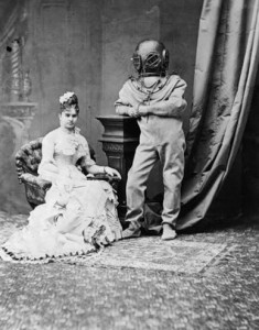 Woman in C19th costume in ornate room with a man in old fashioned diving costume