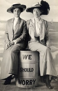 """Two women in late C19th or early C20th dress sitting on a barrel with the words """"We should Worry""""painted on it"""